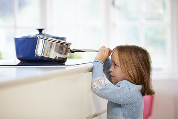 Child trying to take pan off of stove
